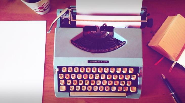 Máquina de escrever, ao lado livro, papel e caneta
