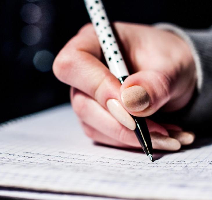 Mão segurando uma caneta escrever